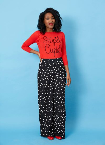 Red 'stupid cupid' slogan jumper and Black wide leg pants with white polka dots