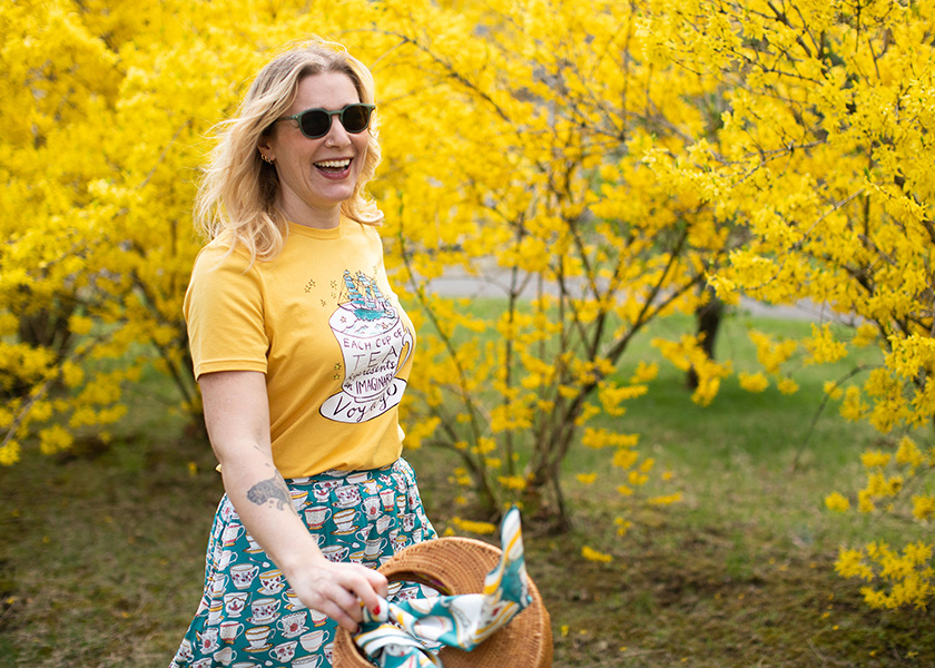 Molly Hatch in front of a yellow tree wearing Rosylea T-shirt and James Teacup print skirt