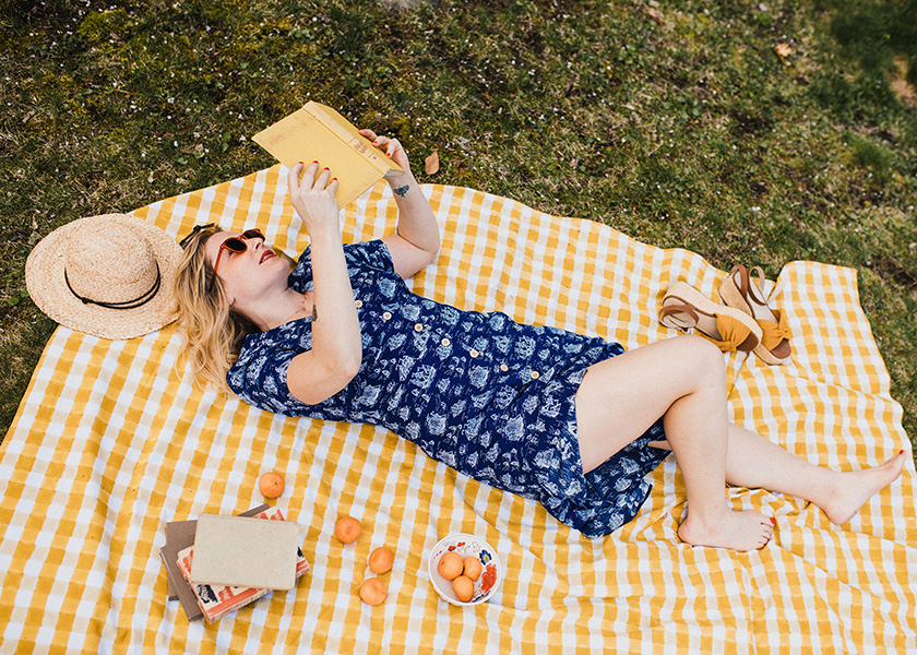 Molly Hatch laying on a picnic blanket reading a book wearing Manon Button-Through Dress